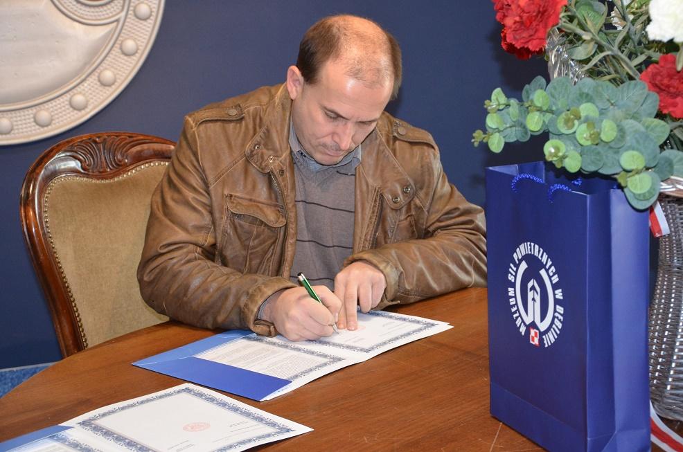 Dariusz Szymanowski podpisuje porozumienie z MSP.